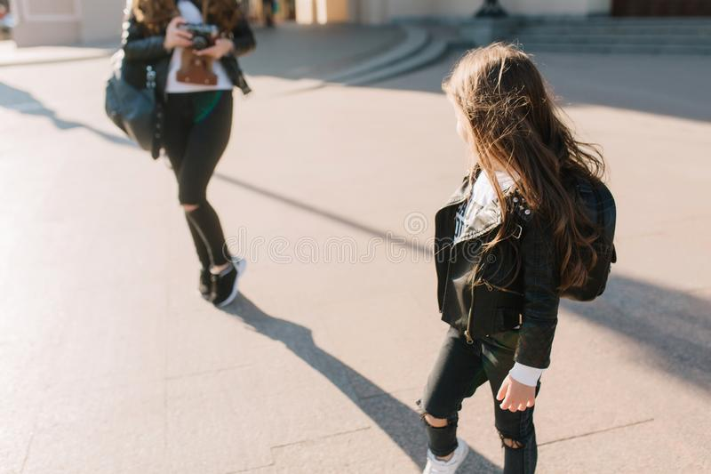 Long-haired brunette girl with school backpack posing on the street after lessons. Shapely woman in black pants holding stock photography