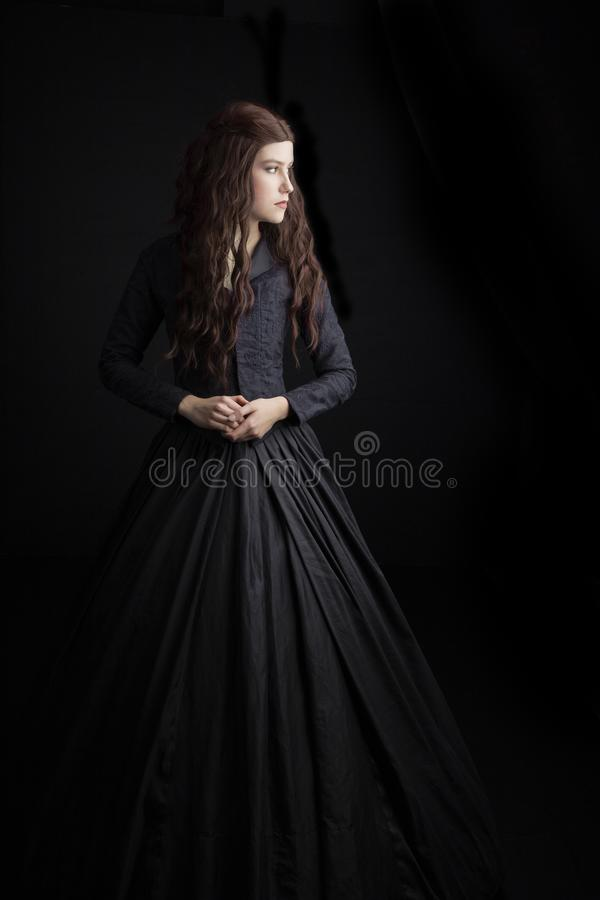 Long-haired, brunette Victorian woman in a black ensemble. Long-haired Victorian woman in a black ensemble. This image had a Gothic feel and would be suitable stock photo