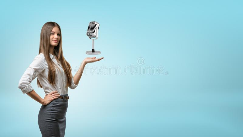 A long haired businesswoman holds out his hand for a metal retro microphone. royalty free stock photos