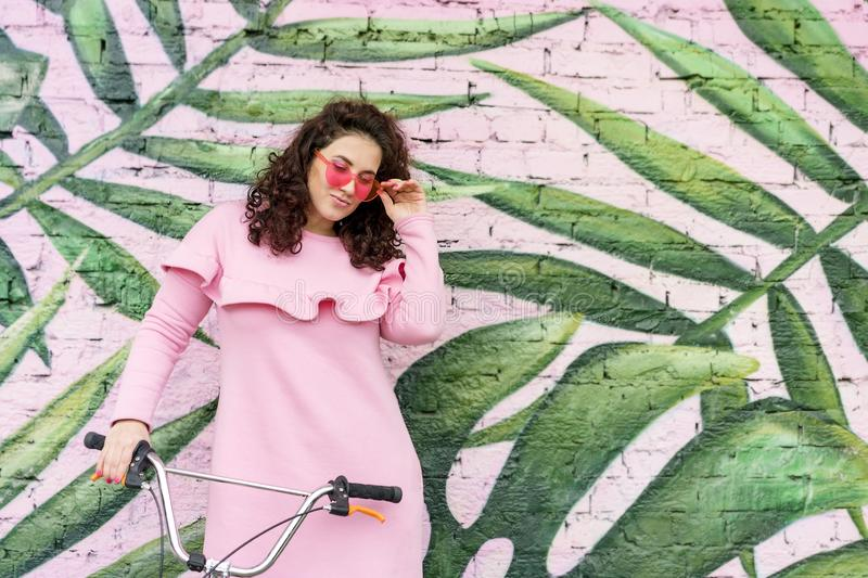 Long haired curly brunette woman in pink dress and pink glasses stock photography