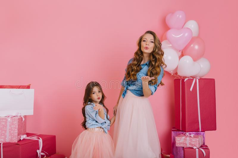 Long-haired curly elegant woman and her lovely child sending air kisses while having fun at birthday event. Stylish mom royalty free stock photography