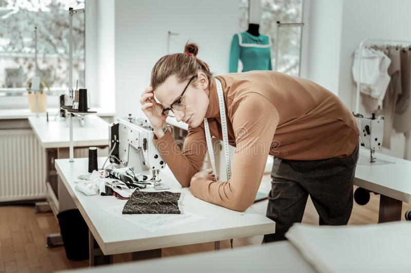 Long-haired fashion dressmaker in a brown garment looking thoughtful. Creative mood. Long-haired fashion dressmaker in a brown garment looking thoughtful while royalty free stock image