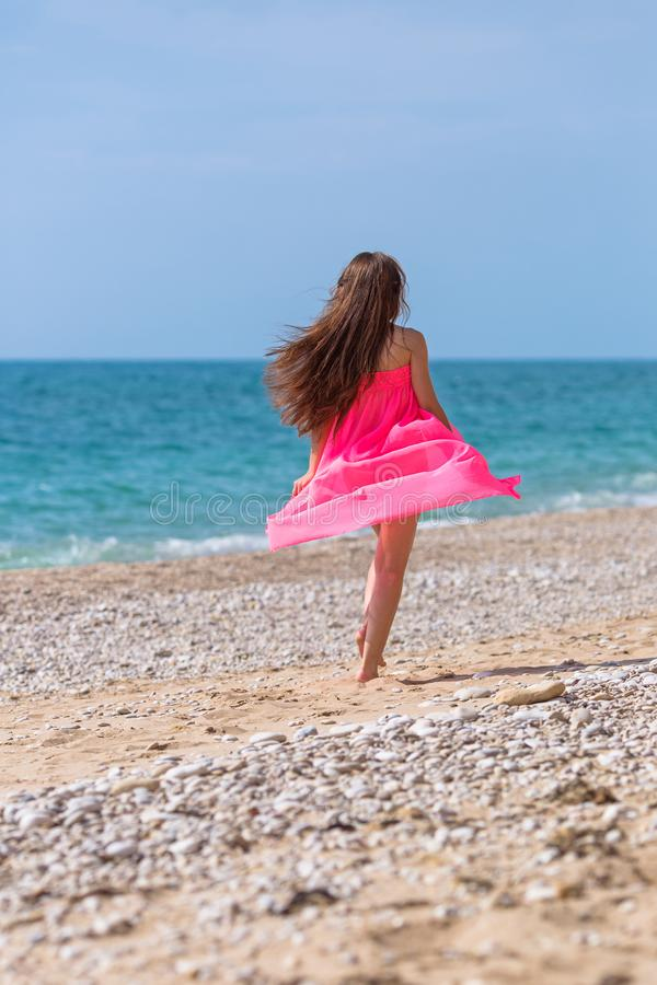 Girl in pink dress running along pebble beach stock images