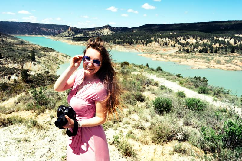 Long-haired female tourist in a pink dress with a camera stands in the mountains stock photo