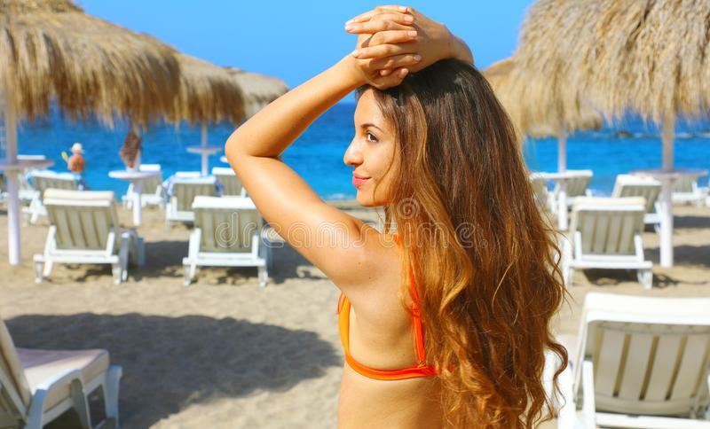 Long haired girl in bikini enjoying on tropical beach.  royalty free stock images