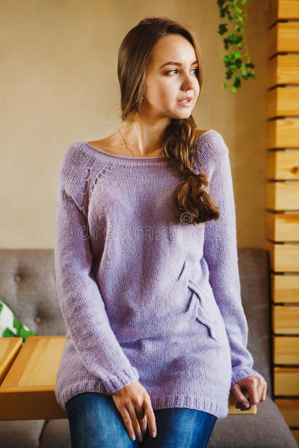 Long haired girl with braid, in long purple sweater and blue jeans royalty free stock image