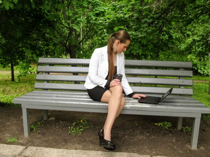 Long-haired girl in a business suit sits sideways on a bench with her legs crossed, holds coffee and looks at the laptop screen, stock image