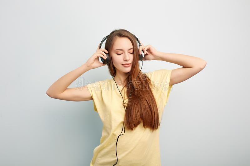 Long haired girl with headphones on her head dressed in a yellow t-shirt and jeans stands on a white background in the stock images
