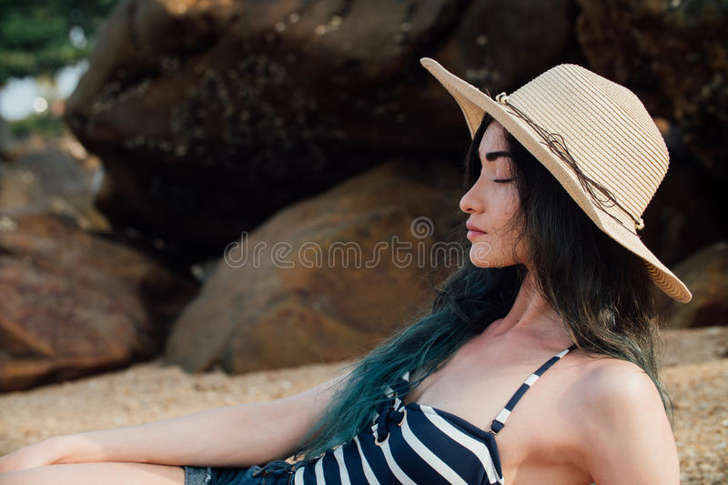 Long haired girl In a hipster hat and striped swimsuit relax on tropical beach, background of stones. stock photography