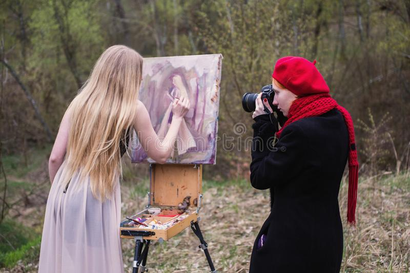 Long-haired girl in the lens of the camera artist paints in oils on canvas self portrait stock photo