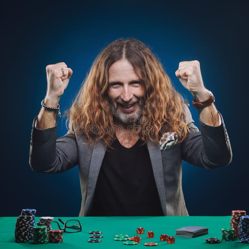 Long-haired handsome man playing poker in a casino royalty free stock photos