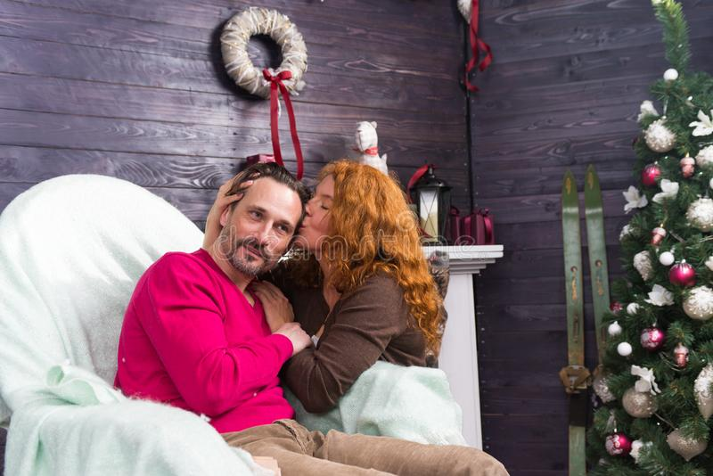 Long haired lady closing her eyes and kissing head of her husband. Calm relaxed bearded men sitting in the armchair and smiling while his beloved women sitting stock photos