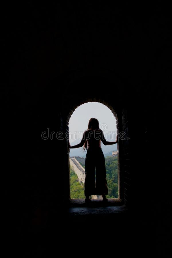 Silhouette of long haired lady in flares against Great Wall of China stock image