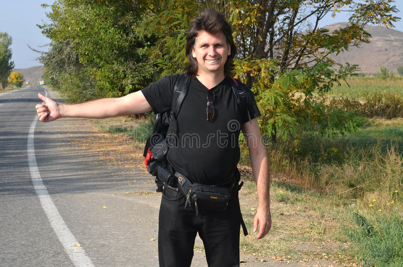 Long-haired man with a backpack catches the car. On the roadside stock photos