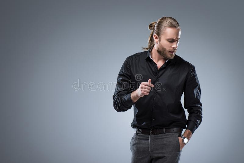 Long haired man in black shirt looking down with hand in pocket, isolated on gray royalty free stock photography