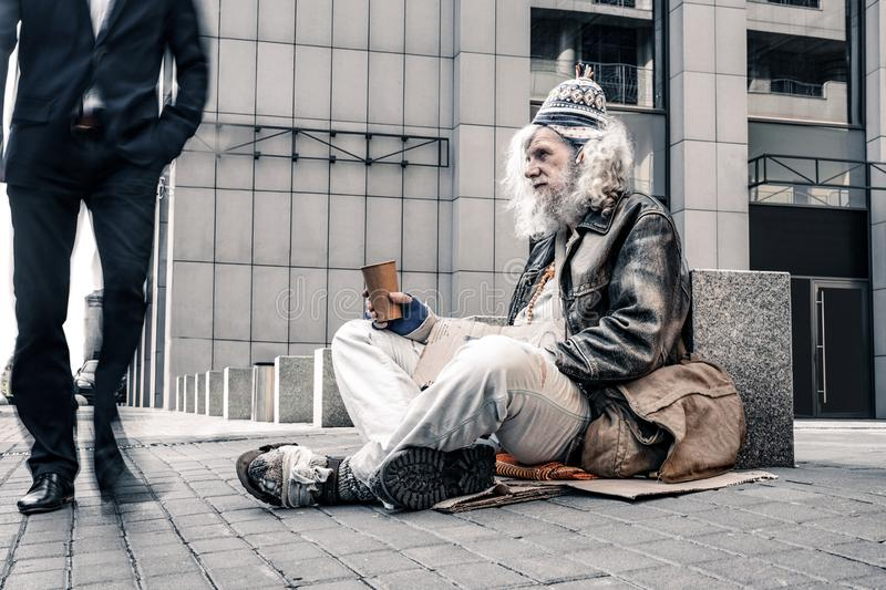 Miserable grey-haired old homeless motionlessly sitting on cold ground royalty free stock photo