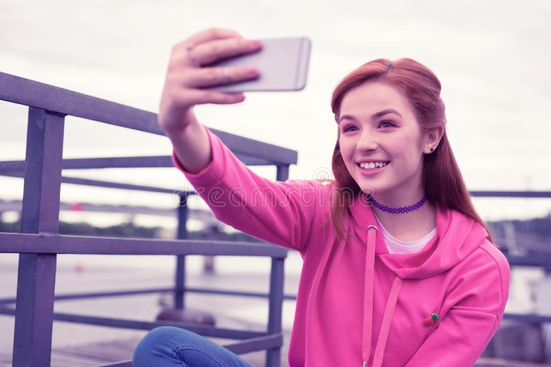 Long-haired pretty girl wearing bright pink hoodie and making selfie. Peaceful good-looking girl. Long-haired pretty girl wearing bright pink hoodie and making stock image