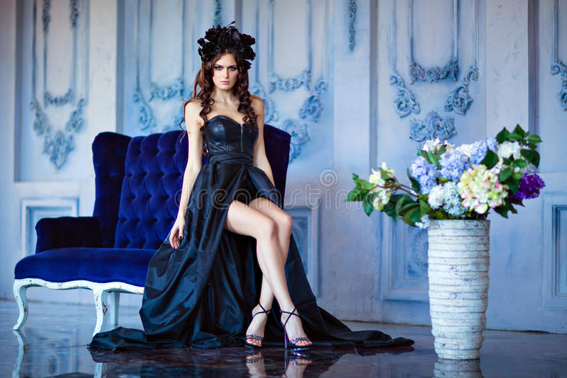 Long haired sensual brunette with a wreath of black flowers sitting on a blue sofa royalty free stock photography