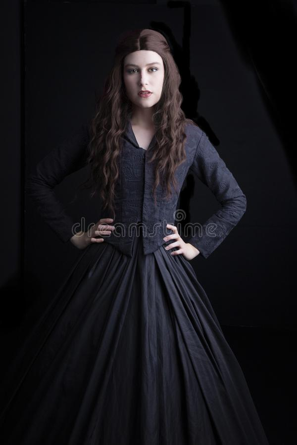 Long-haired, brunette Victorian woman in a black ensemble. Long-haired Victorian woman in a black ensemble. This image had a Gothic feel and would be suitable stock images