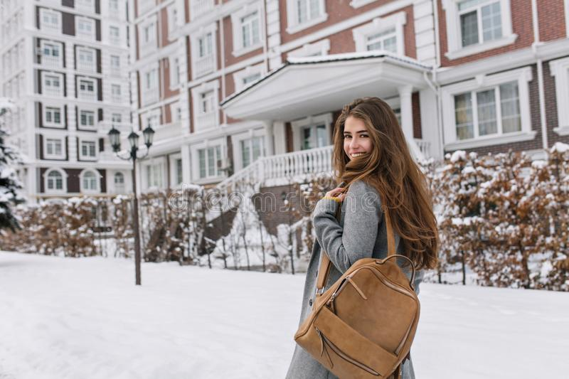 Long-haired woman with brown backpack walking past beautiful building in winter day. Outdoor portrait of wonderful royalty free stock images