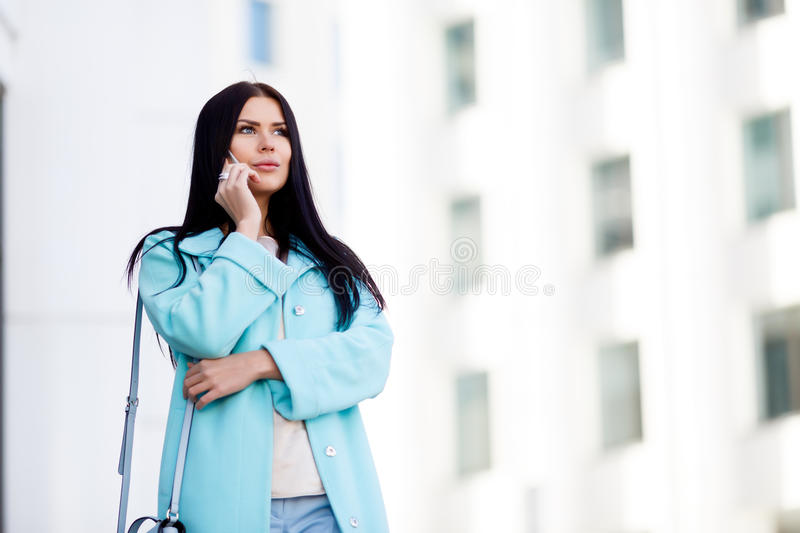 Long-haired woman with phone outdoors stock photography