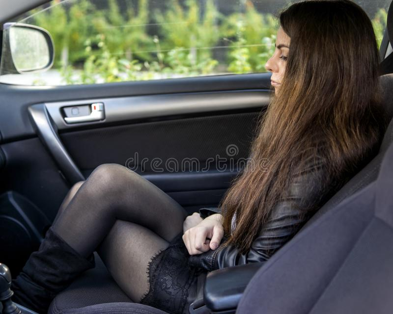 Young girl with seductive legs in black pantyhose and short skirt in car stock photos