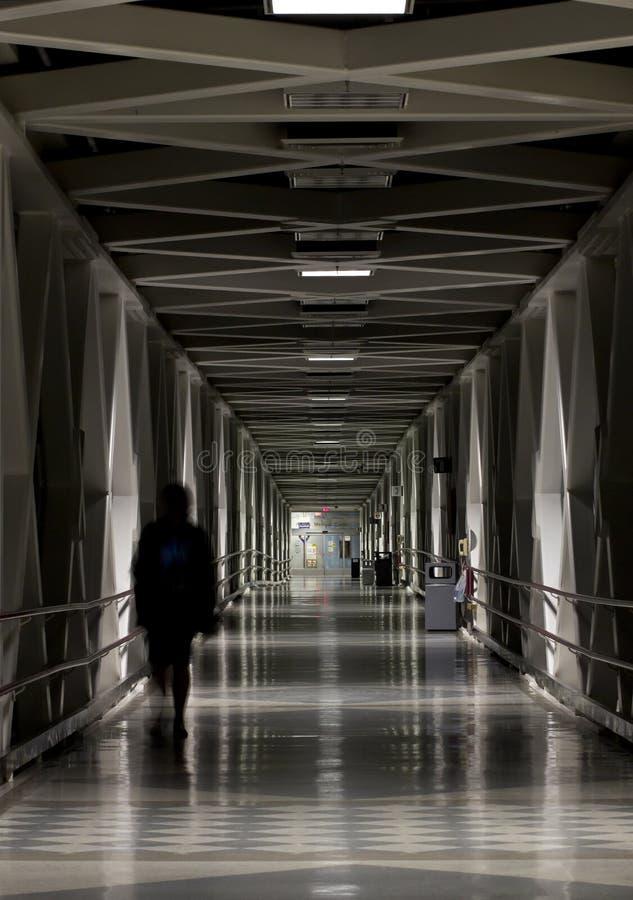 Long Hallway Corridor Passage At Night. Shadow of a person walking down a long corridor at night royalty free stock images