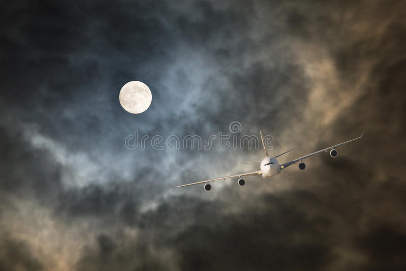 Long-haul night flight through clouds in light of full moon. Passenger jet airliner makes non-stop night flight in the light of full moon to long-haul and long royalty free stock photography