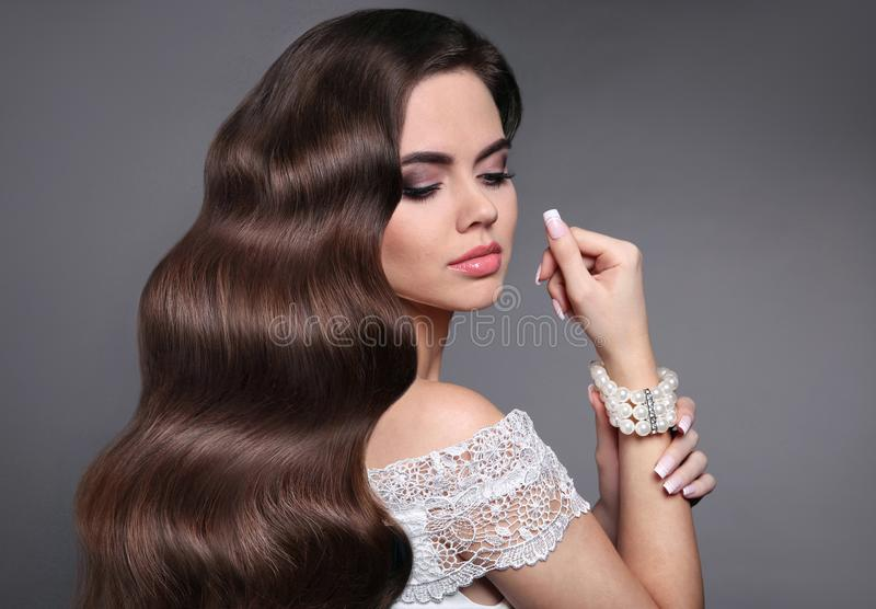 Long healthy wavy hair. Beautiful hairstyle. Beauty makeup. Brunette girl model with shiny curly hair style. Fashion pearl stock photography