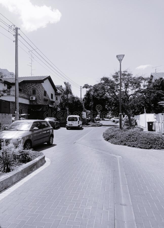 Long view of street. Long high angle view from street with residential houses and parking cars along paved road in daytime stock photography