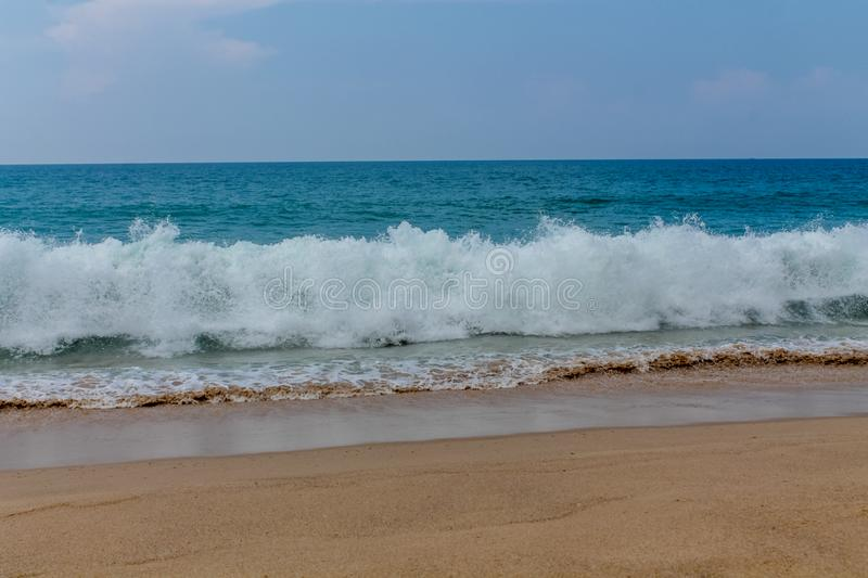 Ocean high tide waves on sandy beach. Long and high sea ocean tide waves on sandy beach with white sea foam stock images