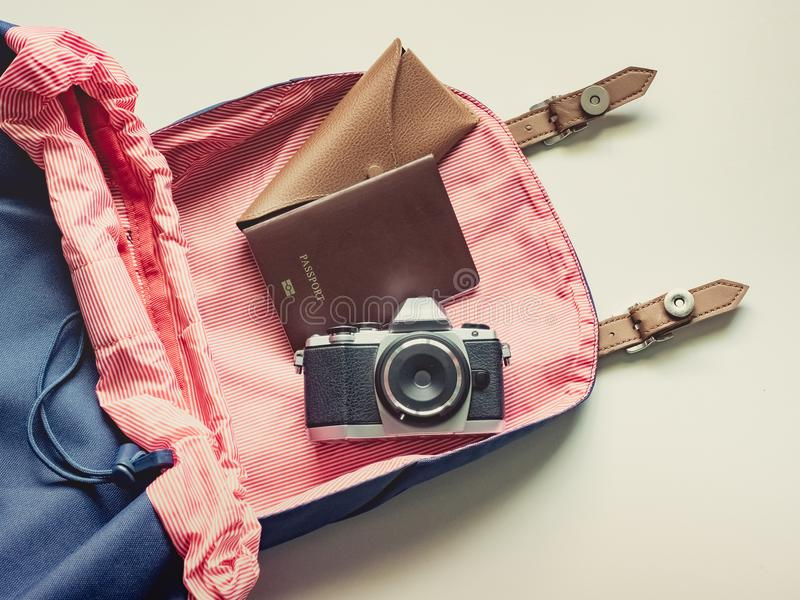 long holiday travel flat lay concept from blue backpack with retro camera , sunglasses with case and passport put on isolated stock photography