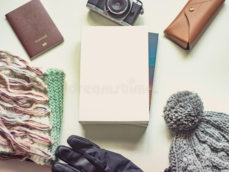 Long holiday and winter season travel flat lay concept from winter cloth item and passport , retro camera , sunglasses and book p. Ut on isolated white stock image