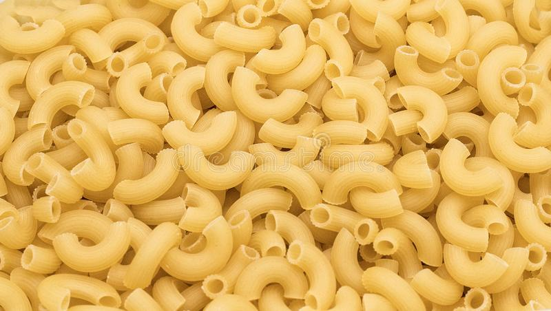 Long horns pasta in in quantities - macaroni texture. Background stock image