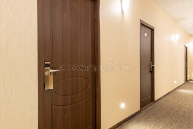 Long hotel corridor accent on the door. Hall, hallway, interior, architecture, doors, empty, light, nobody, carpet, horizontal, motel, inside, travel, tunnel stock photography