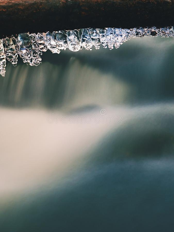 Long icicles hang above dark freeze water of mountain stream. Winter season at river, thin icicles are hanging on fallen trunk above milky water level stock photos