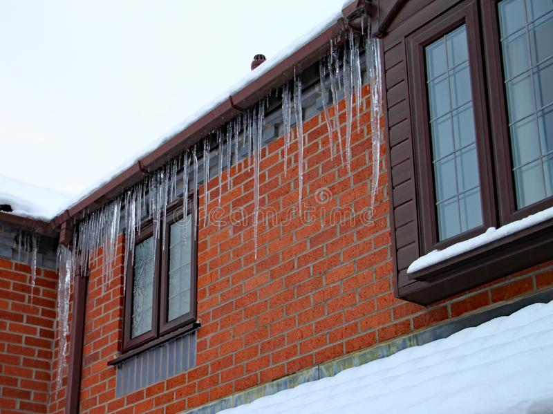 Long icicles hang from the gutter of a house. The roof is covered in snow and it`s still snowing royalty free stock photos