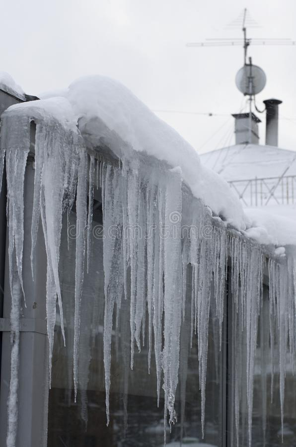Long icicles hang from the roof of the house stock image