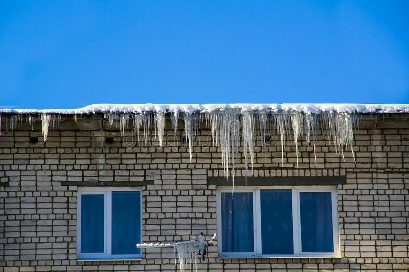 Long icicles and snow hang on the eaves of the house roof stock photography