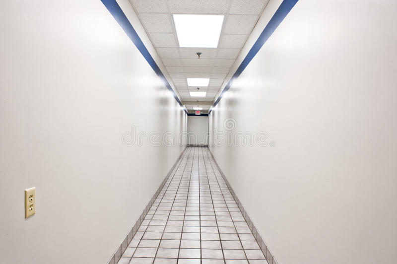 Long Intimidating Hallway. A long intimidating lighted hallway with electrical plug on the wall royalty free stock photos