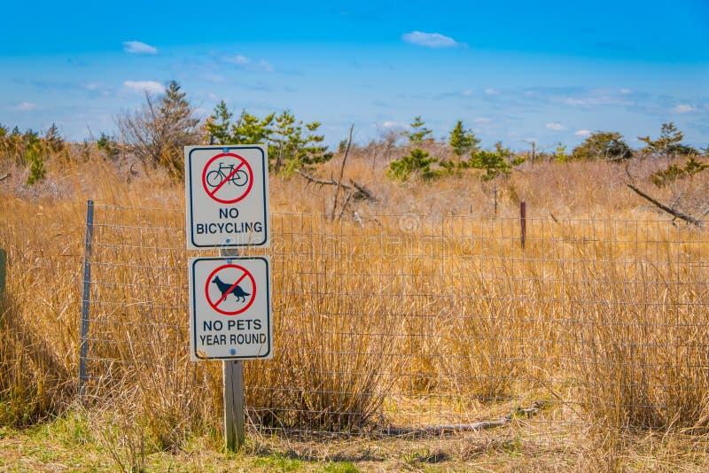 LONG ISLAND, EUA, ABRIL, 17, 2018: Ideia exterior do sinal informativo nenhuns bicycling e não animais de estimação na área na fotos de stock