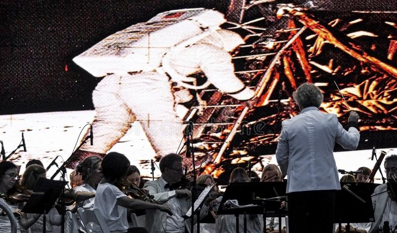 Long Island Orchestra performing with picture of moon landing in background. East Islip, NY, USA - 13 July 2019: The Long Island Concert Orchestra performs for stock photo