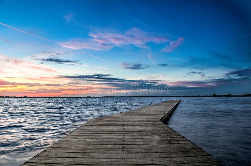 Long jetty extending over lake royalty free stock images