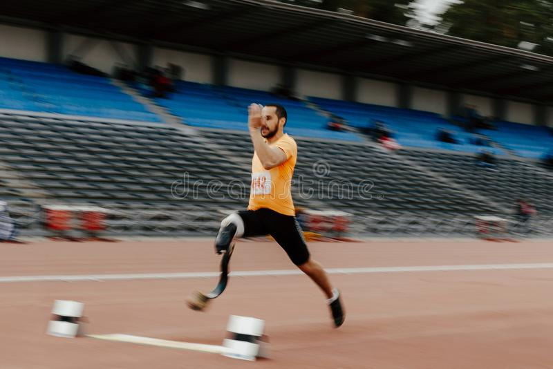 Long jump athlete disabled amputee. Track and field competition stock image