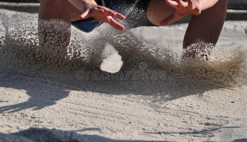 Long Jump Athlete Landing. In the Sand royalty free stock images
