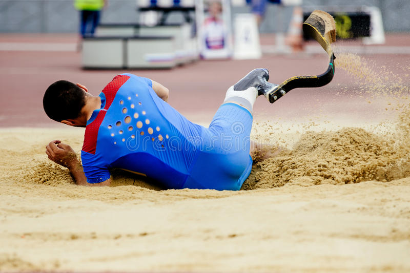 Long jump athlete paralympic. Disabled landing in sand stock image