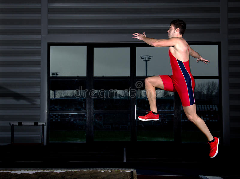 Long jump athlete. Training indoor stock photography