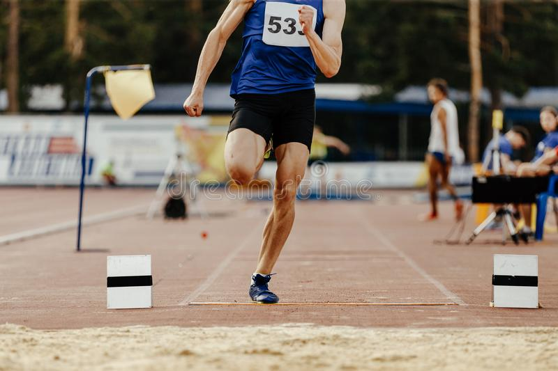 Long jump men athlete jump. In athletics competition stock photo