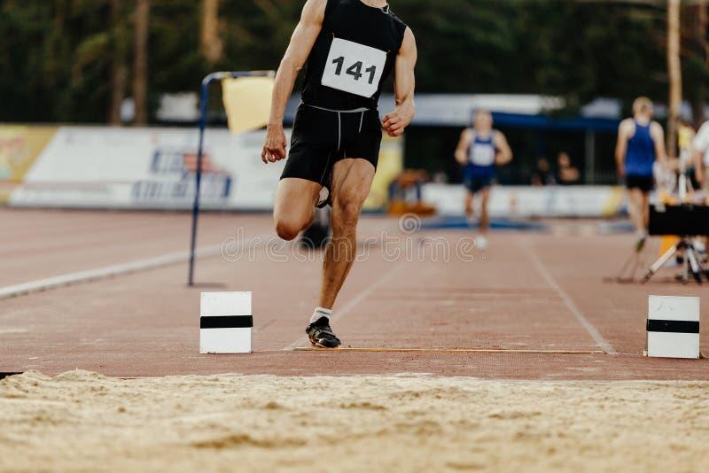 Long jump men athlete. Jumper takeoff board royalty free stock images