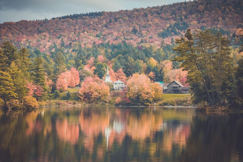 A white church steeple stands out among brilliant fall foliage in Long Lake, NY. Long Lake, Adirondacks, NY, in the fall surrounded by foliage royalty free stock images